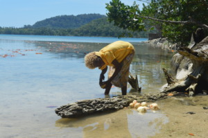 Girl use sea to clean sweet potatoe for lunch