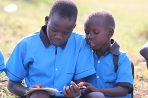 Two young students read a book provided by RtL