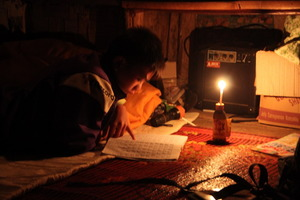 A resident studies by candlelight