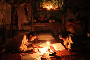 Children studying using kerosene lamps as lighting