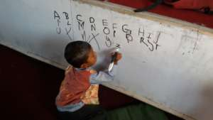 Young boy practices his writing
