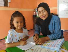 Fitriyah is giving tutorial to the younger student