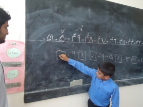 A disabled child writing numbers on the board
