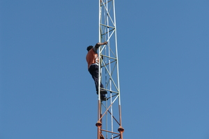 A technician on a mesh tower