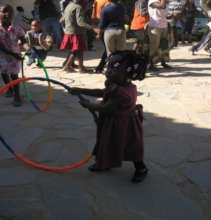 A little girl learning to hula hoop