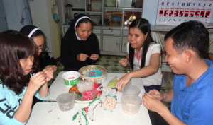 Tinh (blue T-shirt) is learning to make crafts