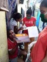 Distributing Textbooks to girls in bastis