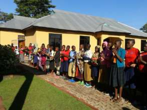 Resident girls sing a welcome