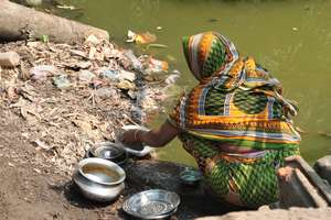 Woman washing dishes in the pond