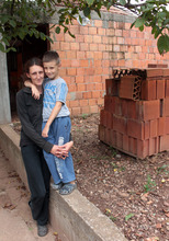 Andrija and his mother with the bricks for toilet.