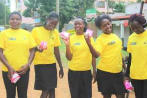 Some girls proudly holding  boxes of sanitary pads