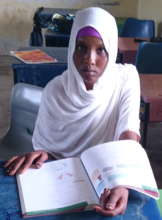 Fatuma with textbook provided by the foundation