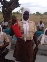 A student from Buyani with her pack of napkins