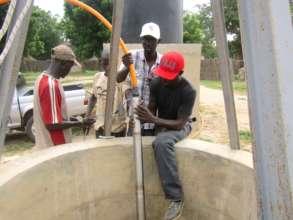 CREATE! technicians install the solar-powered pump