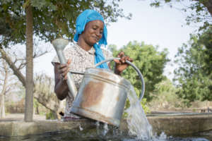 Woman filling up her watering can from the basin