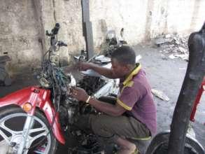 Auwal's Employee Working on Motorcycle Repair