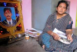 Mrs Rajalakshmi with a photo of her son Loganathan