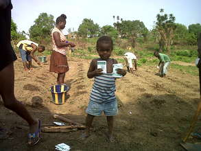 Child with seeds in garden, Liberia.