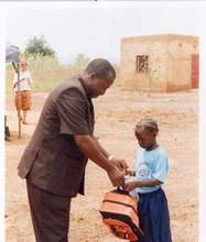 NEEED's Lacine Sawadogo gives a young girl materia