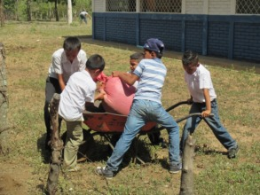 Kids cooperate to lift compost bag