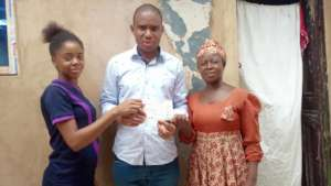 Emeke presents the cheque to Naomi and her mom.