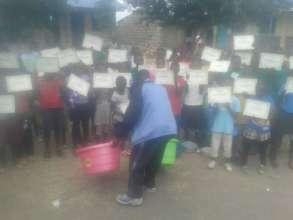 Bwana Juma giving awards to sch. children