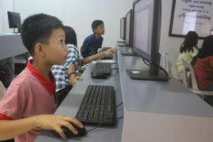 CJFI kid doing computer assignment