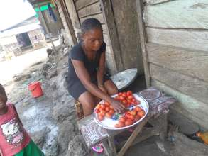 Itsa sells tomatoes in front of her house