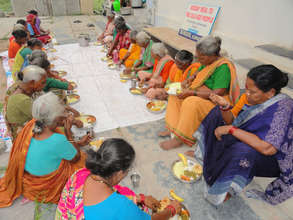 poor elderly persons are having food at daycare