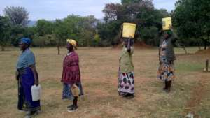 Women wait to gather water.
