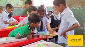 A young girl teaching her fellow classmates ludo!