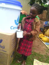 Achild drws water from the new water purifier
