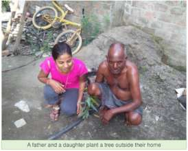 Daughter and father happily plant sapling together