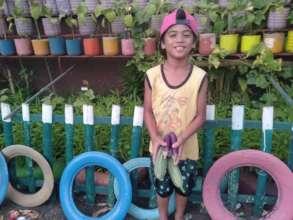 Little gardener enjoys  bounty at Salih Yusah ES