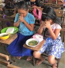 Christian children praying before lunch