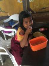 Refugee child happy to be provided with food