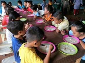 Refugee children enjoying a meal provided by AAI