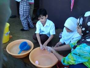 teachers wash with students at Sahaya before lunch