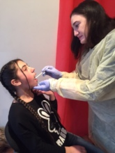 SOAR dental hygenist cleaning teeth and teaching