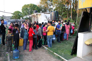Survivors line up for clean drinking water (ECCA)