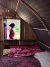 A woman stands outside her new temporary shelter