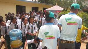 Providing biscuits and juice in Sankhu school