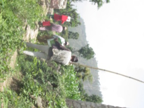 Villagers carry home the cookstove