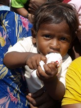 Baby clutching a milk packet donated by Care&Share