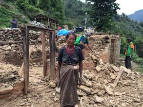 Tamang woman in front of her destroyed house.