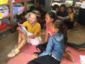 Volunteer Sarah reading with our students