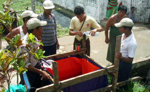 IDE staff trains people in the proper use of the water basket