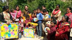 Giving play items to children in Lalitpur