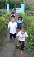 Small students carry water up a steep hill daily