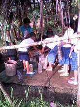 students fill school wash area with hauled water